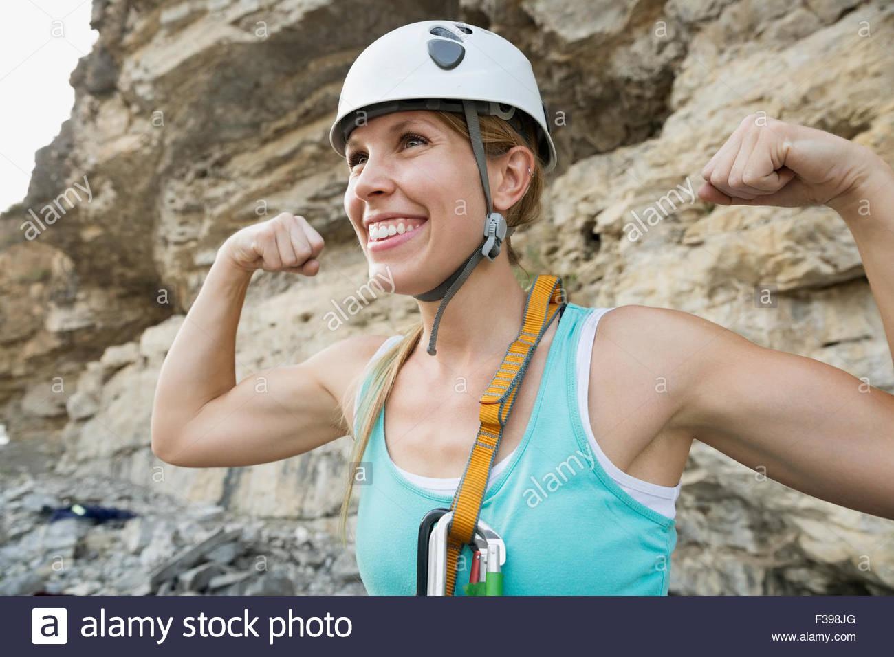 Portrait confident female rock climber flexing biceps - Stock Image