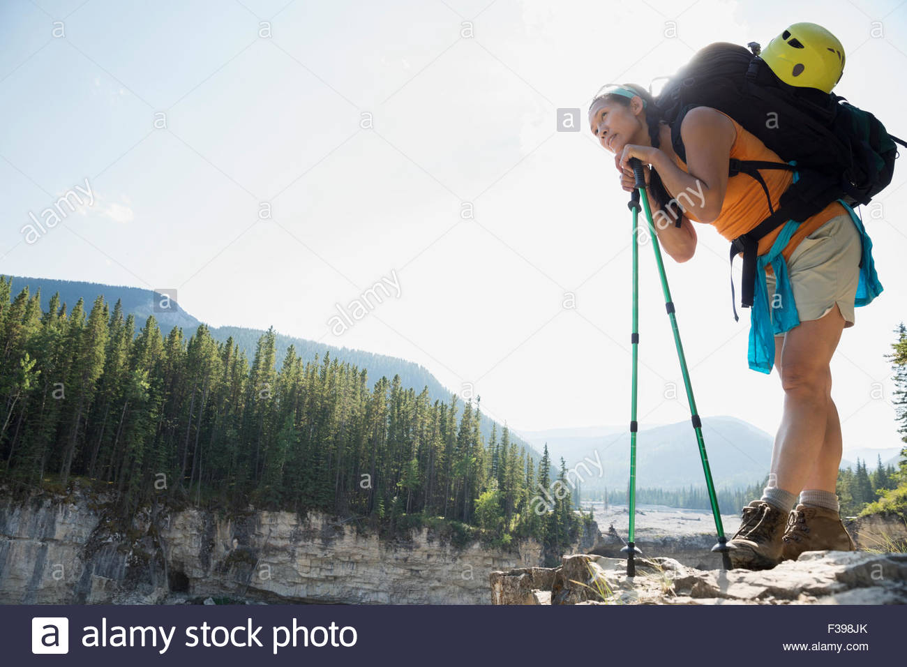 Woman backpacking leaning on hiking poles - Stock Image