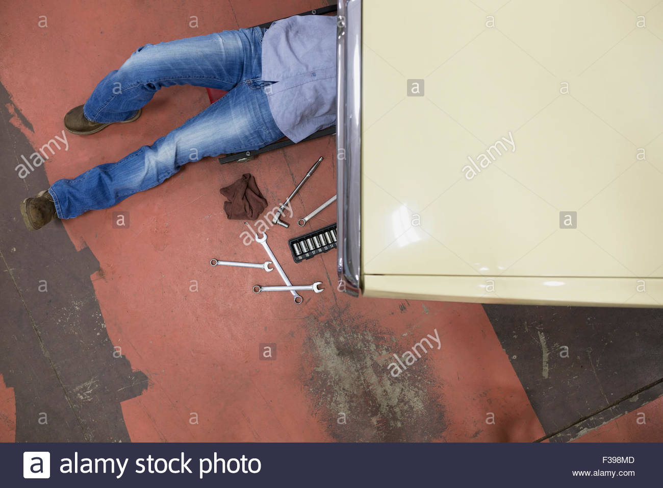 Overhead view female mechanic underneath car - Stock Image