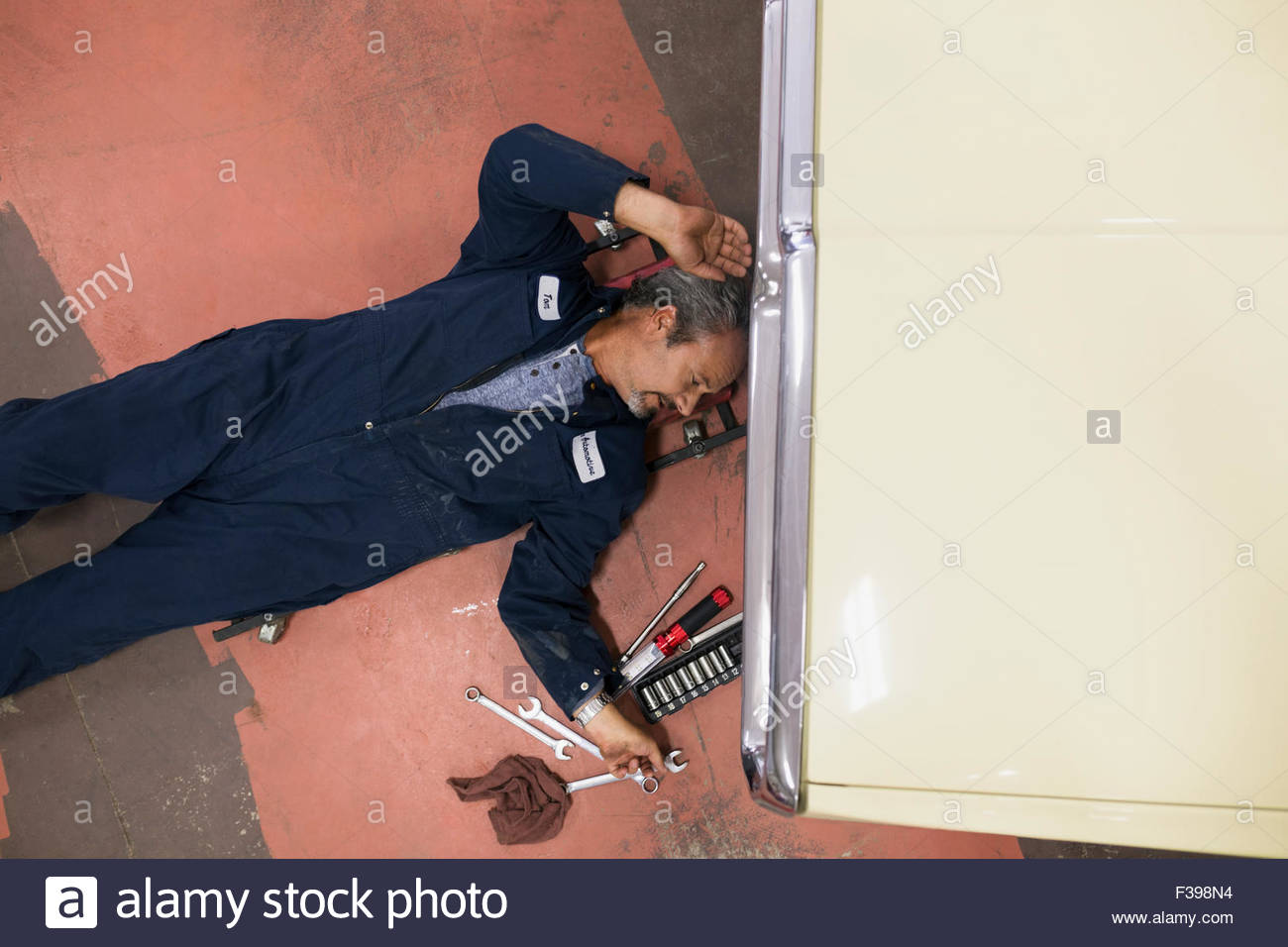 Overhead view mechanic reaching for tool underneath car - Stock Image