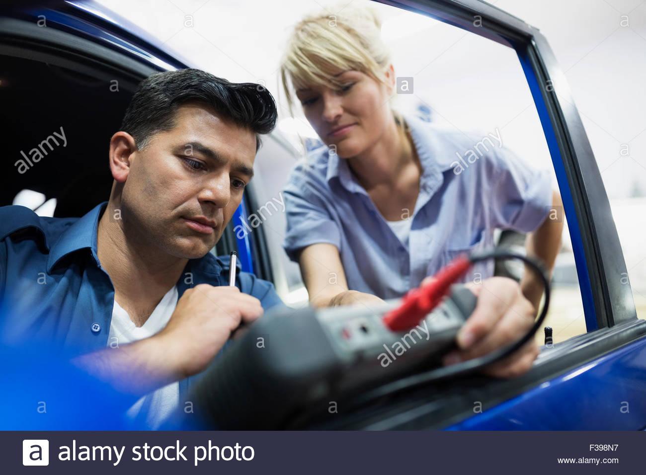 Mechanics diagnostic testing car in auto repair shop - Stock Image