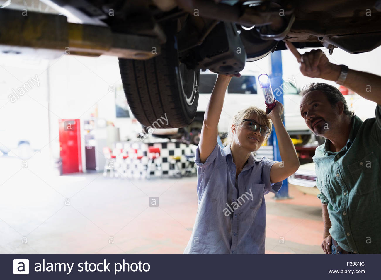Female mechanic and customer underneath car - Stock Image