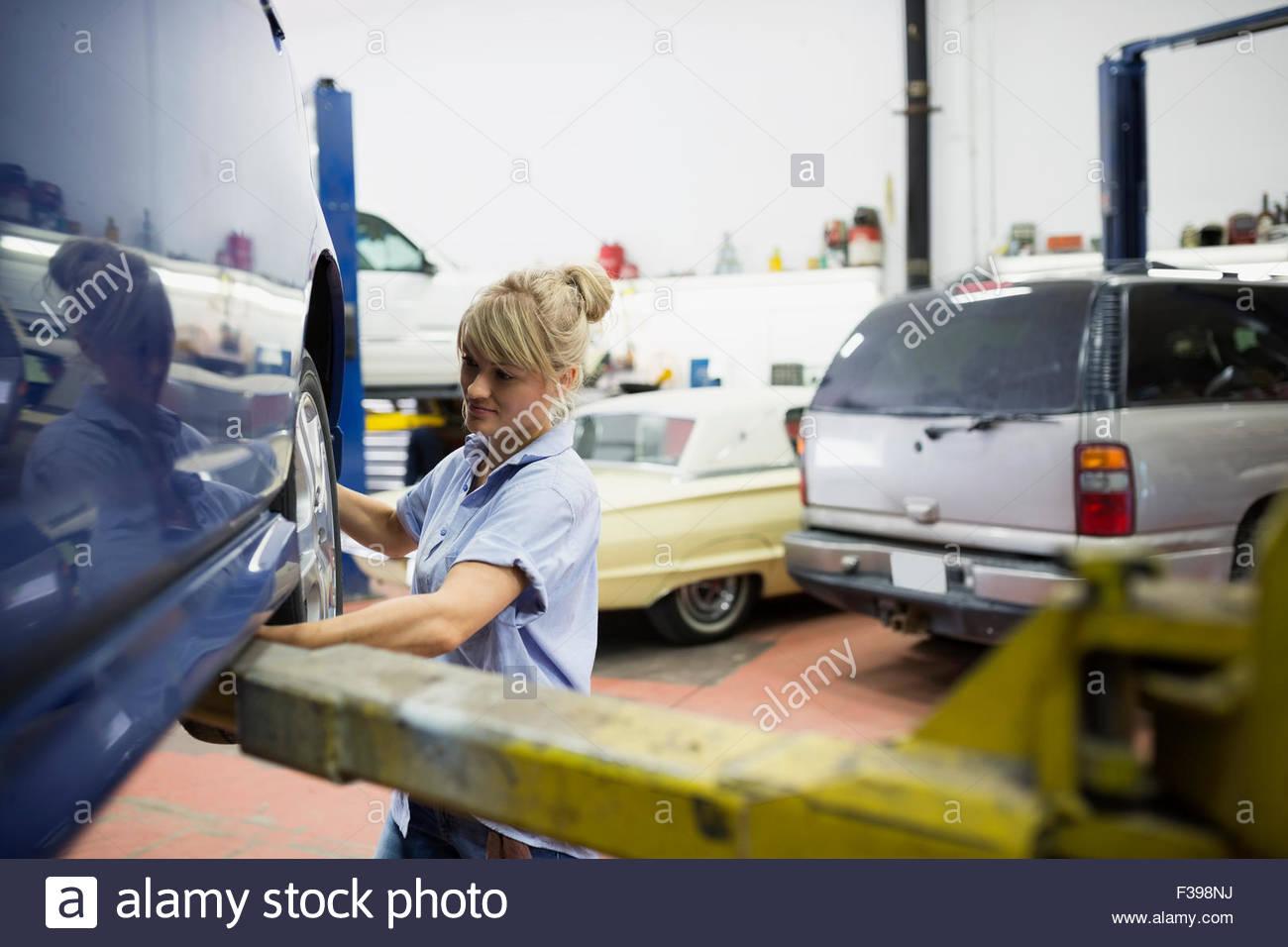 Female mechanic replacing tire on car - Stock Image