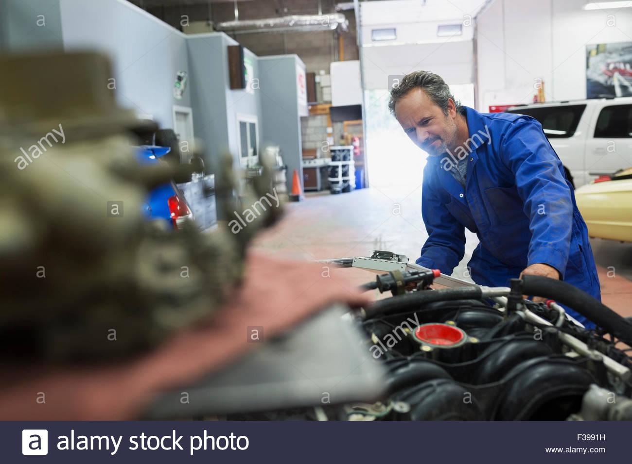 Mechanic examining engine in auto repair shop - Stock Image