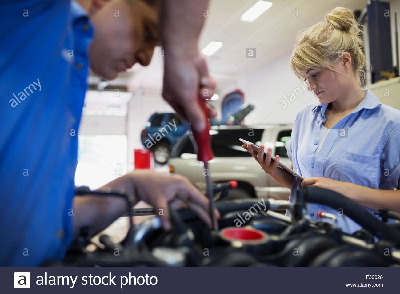 Female mechanic with digital tablet fixing engine - Stock Image