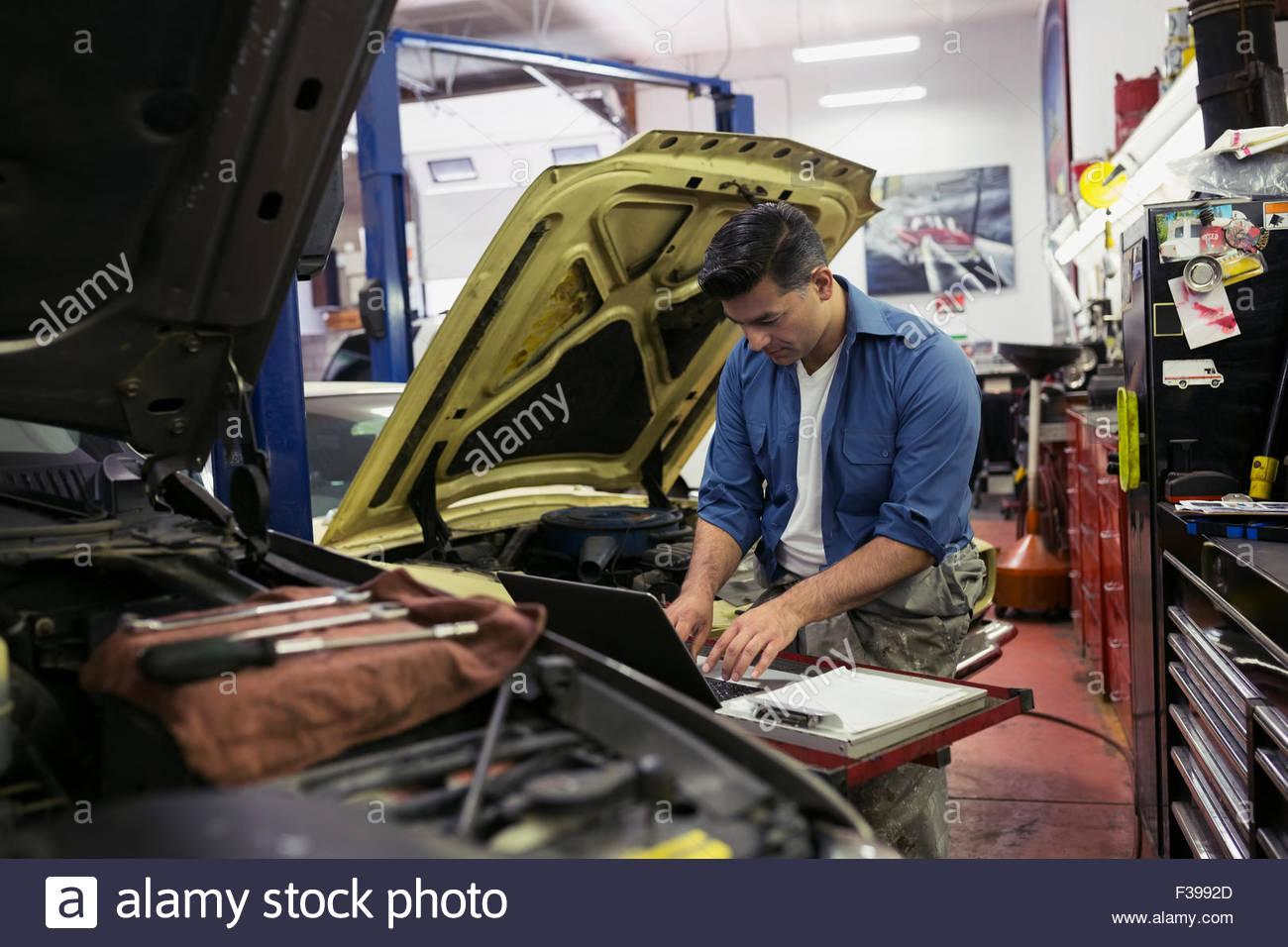 Mechanic diagnostic testing at laptop auto repair shop Stock Photo