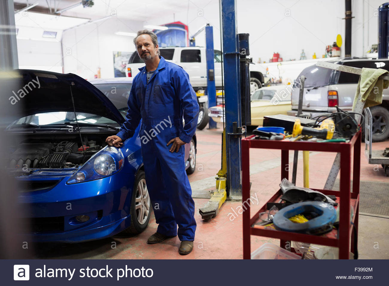 Portrait confident mechanic in auto repair shop - Stock Image