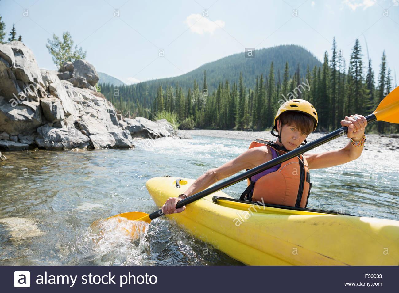 Determined woman kayaking in river - Stock Image