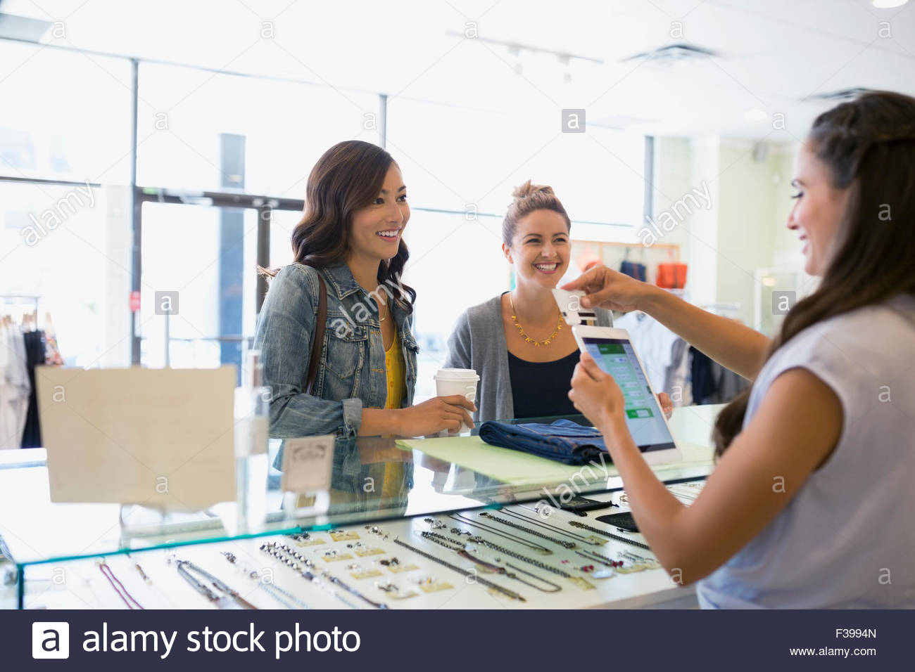Worker swiping credit card reader digital tablet shop - Stock Image