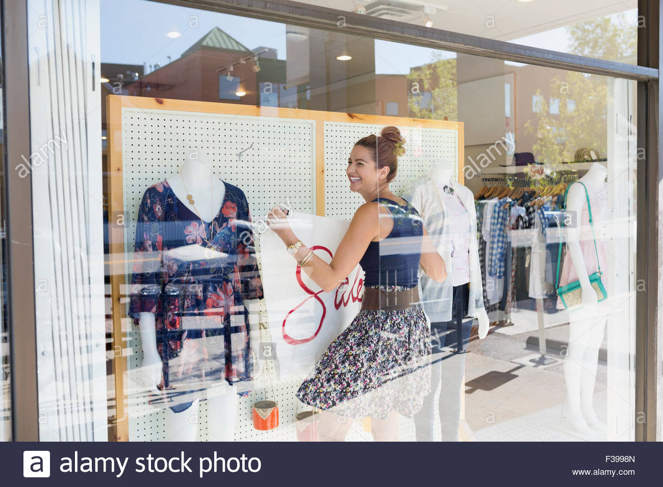 Smiling worker hanging sale sign clothing shop window - Stock Image