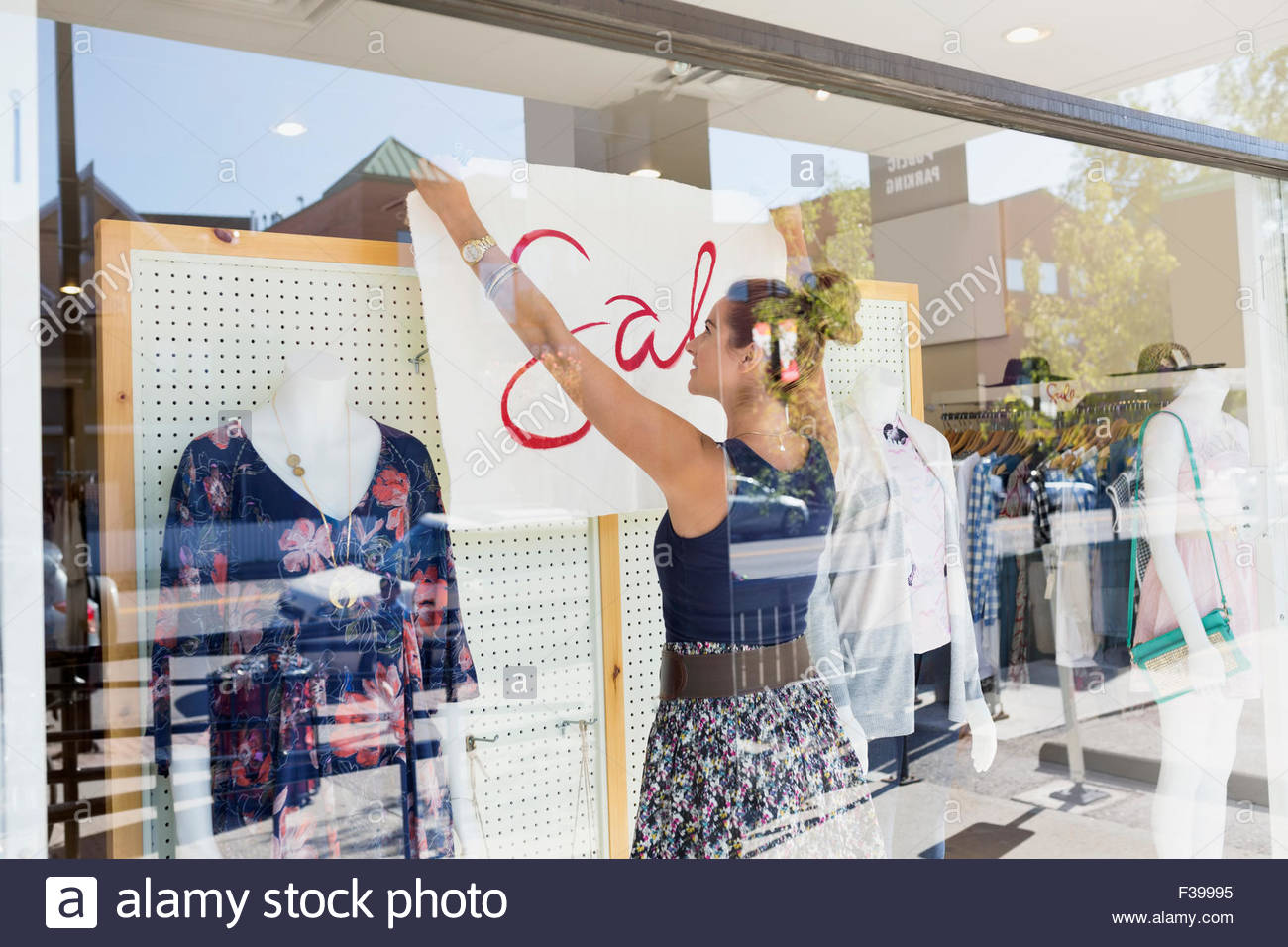 Worker hanging sale sign clothing shop window - Stock Image