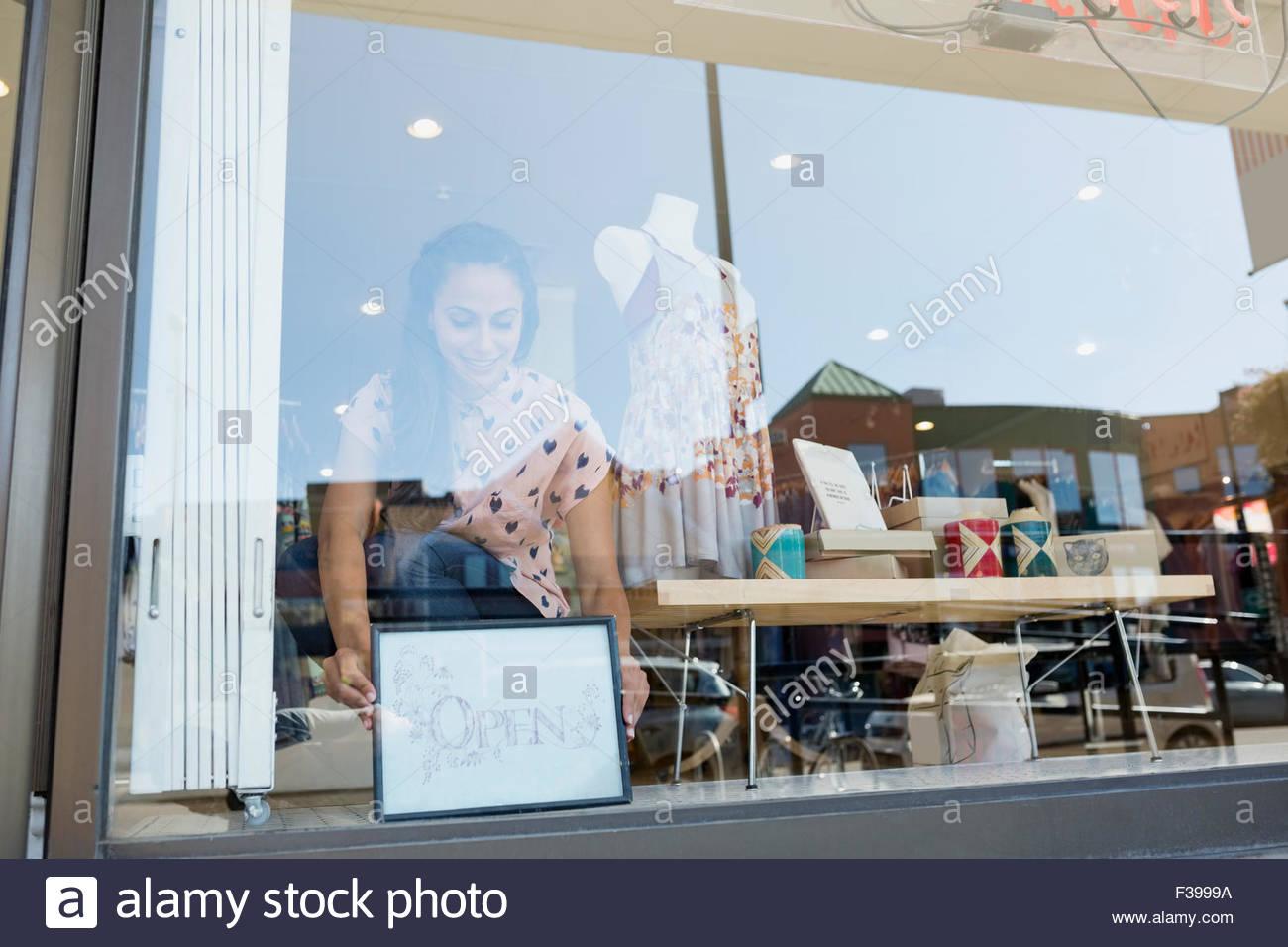 Worker placing open sign in shop window - Stock Image