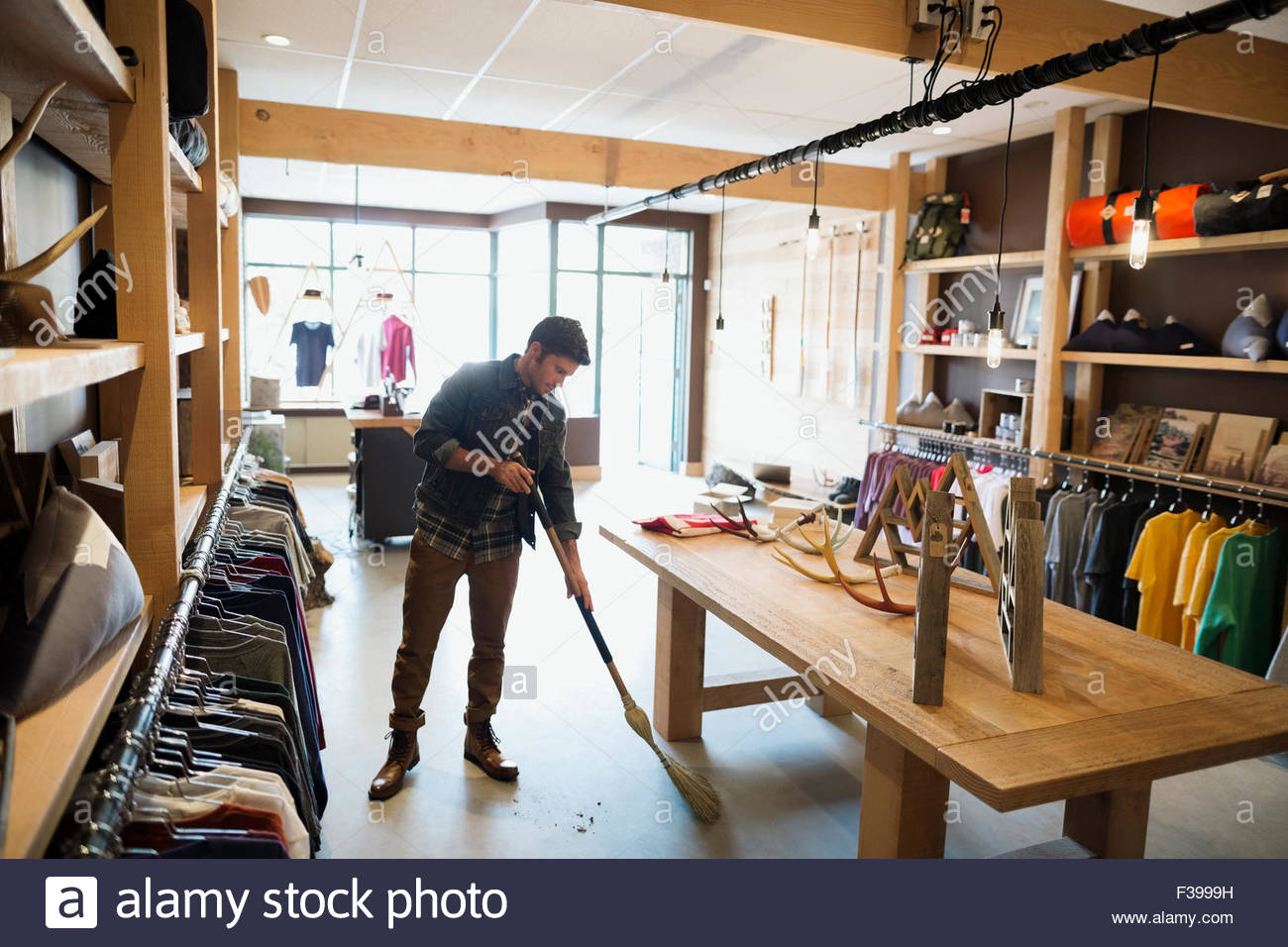 Worker sweeping with broom in shop - Stock Image