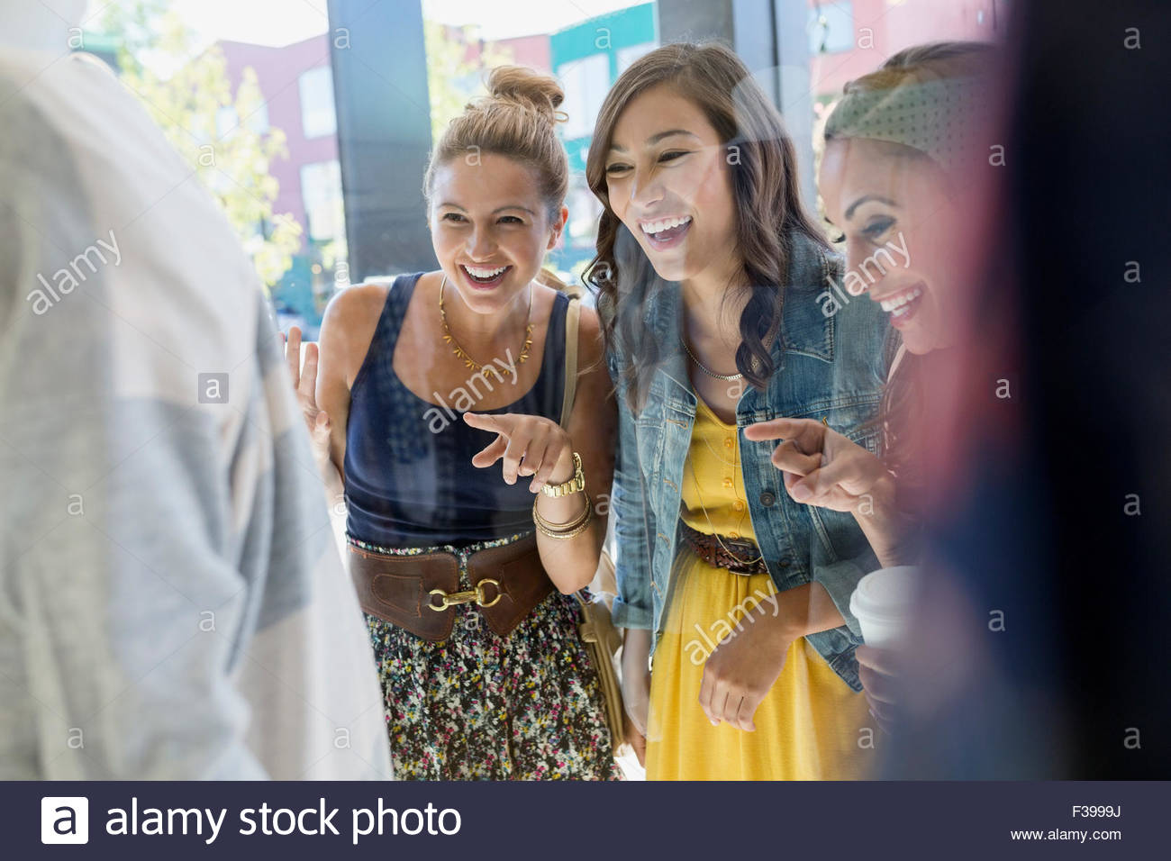 Smiling women window shopping and pointing at storefront - Stock Image