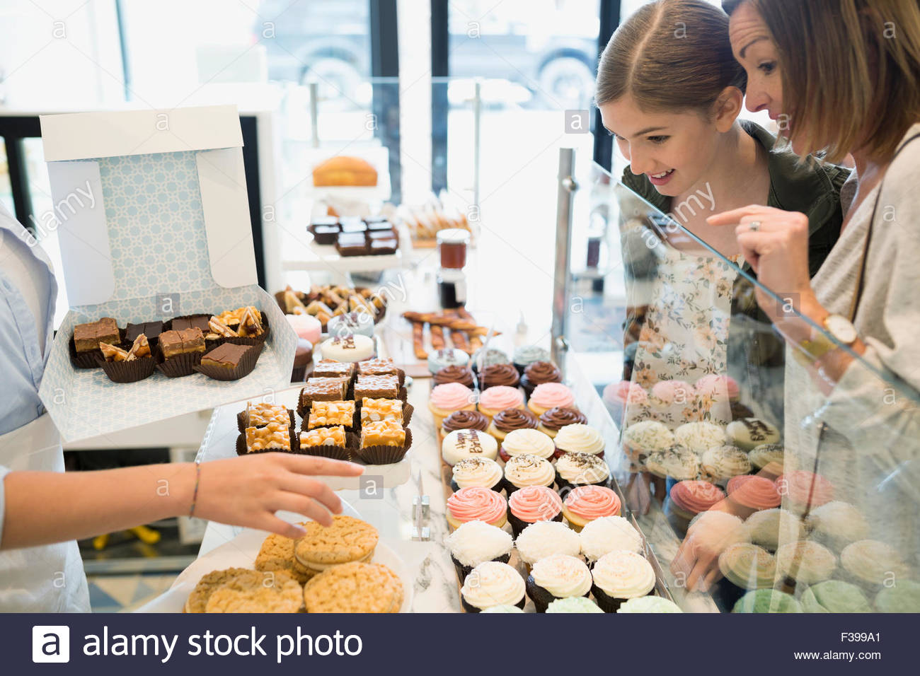 Mother and daughter choosing sweets in bakery - Stock Image