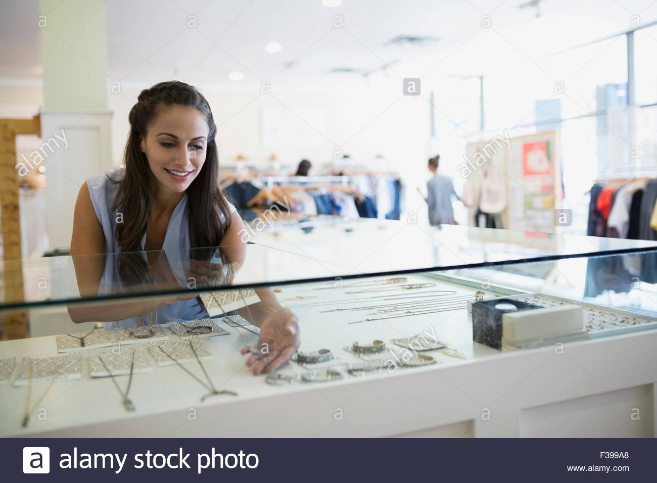 Worker arranging jewelry display case in shop - Stock Image