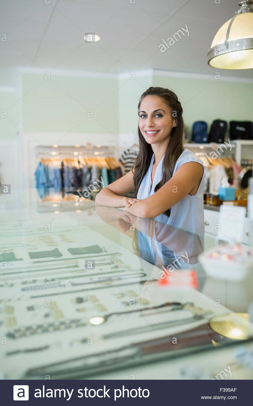 Portrait confident worker at jewelry display case shop - Stock Image