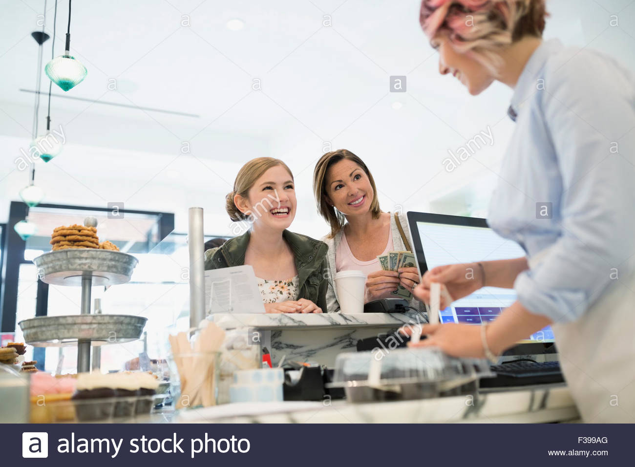 Mother and daughter buying pastries in bakery - Stock Image