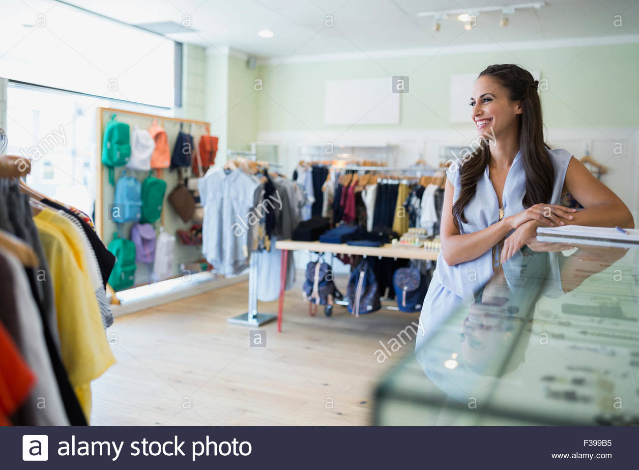 Smiling worker leaning on display case in shop - Stock Image