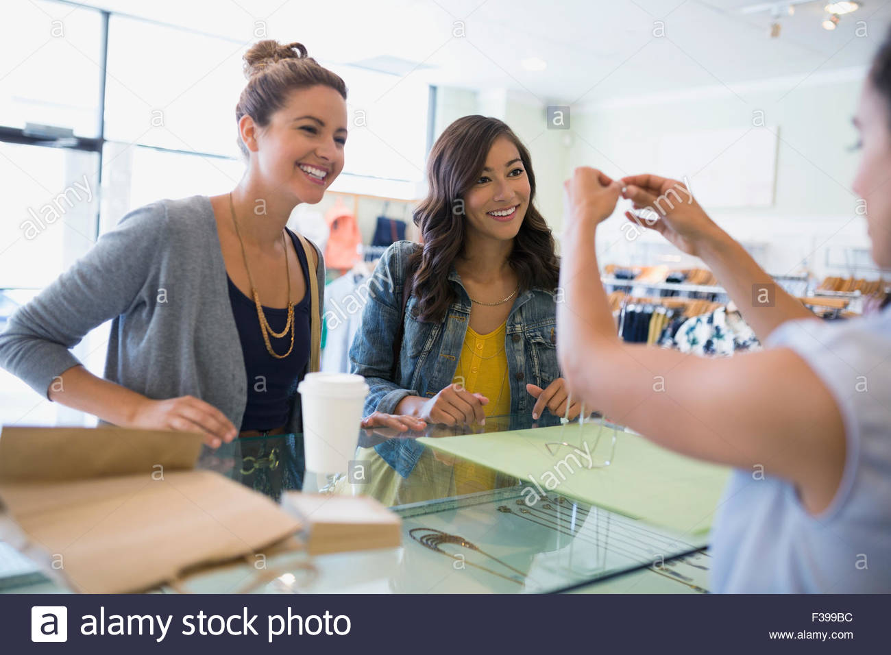 Women buying necklace at shop counter - Stock Image