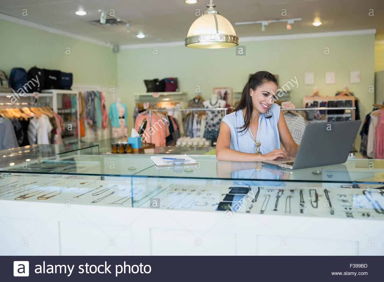 Worker using laptop at counter in shop - Stock Image