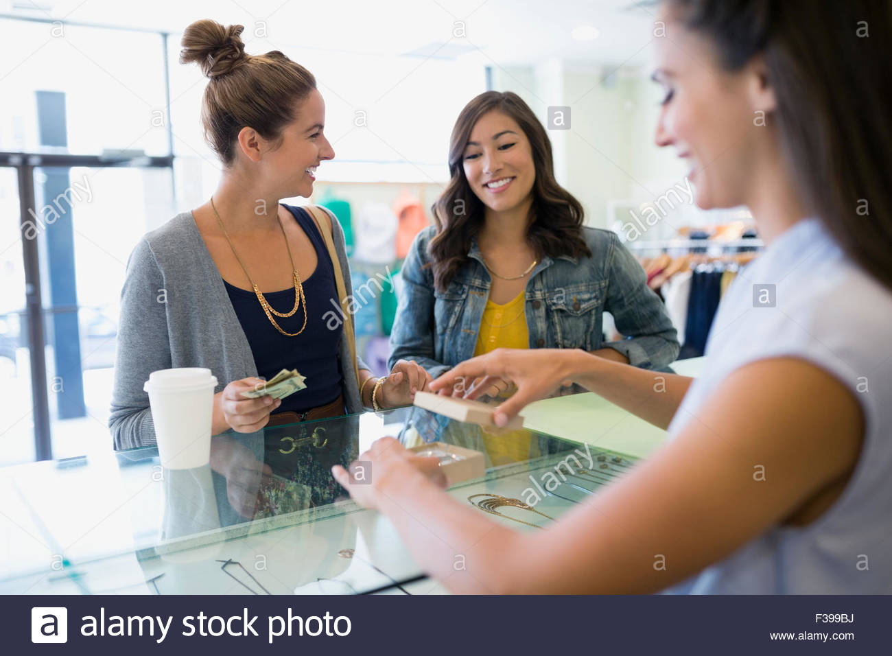 Women buying jewelry at shop counter - Stock Image