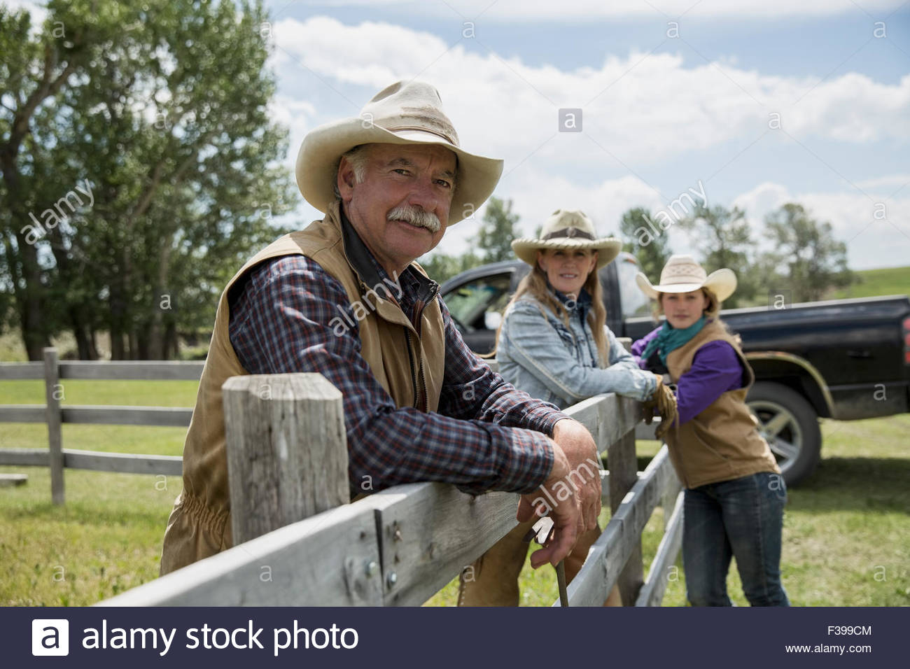 Portrait confident rancher family at rural fence - Stock Image