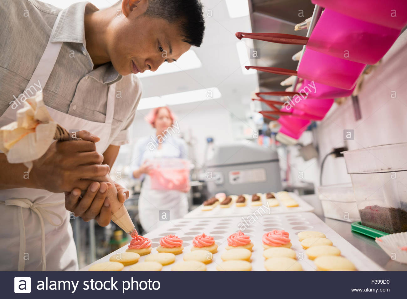 Pastry chef piping cookies pink icing commercial kitchen - Stock Image