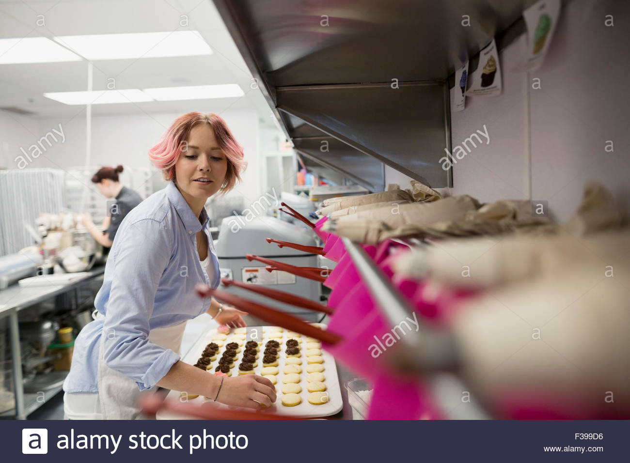 Pastry chef baking cookies in commercial kitchen - Stock Image