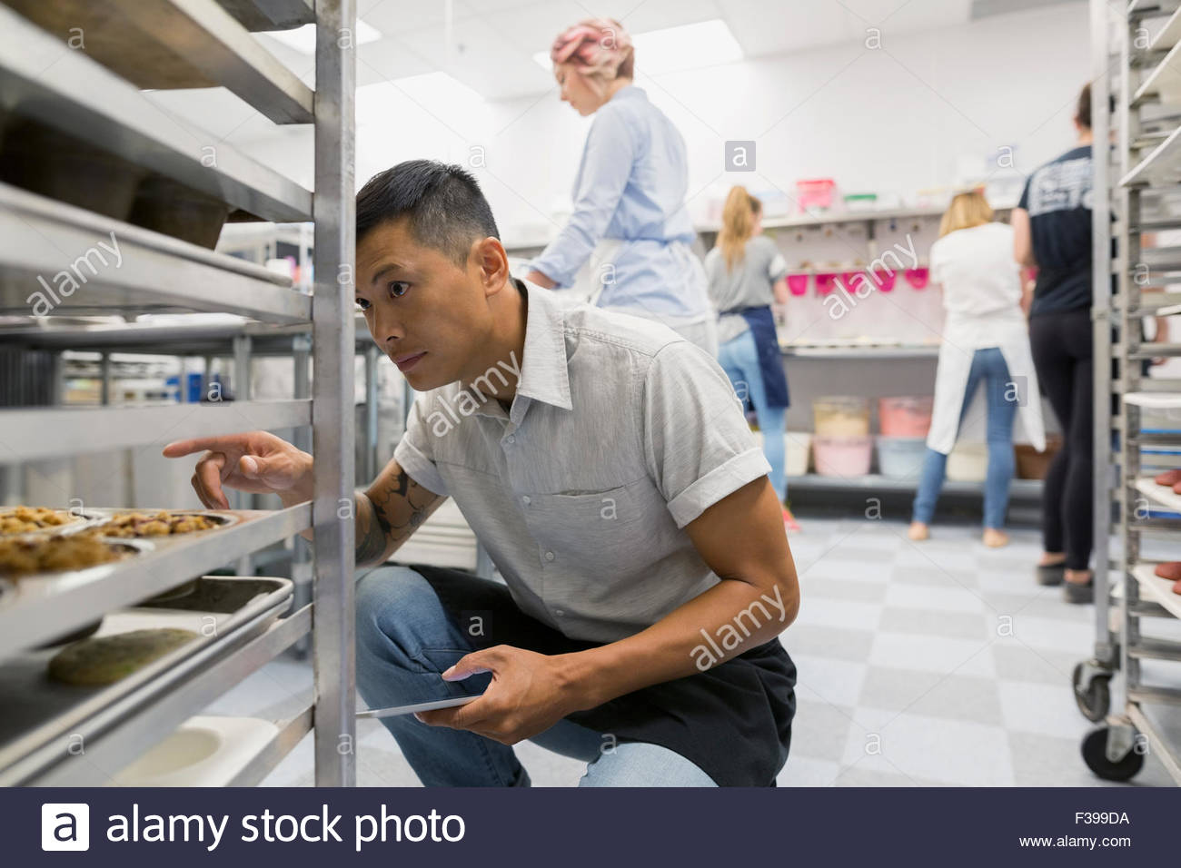 Pastry chef counting muffins on racks commercial kitchen - Stock Image