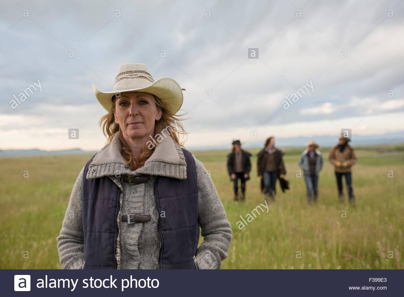Portrait confident female rancher in remote rural field - Stock Image