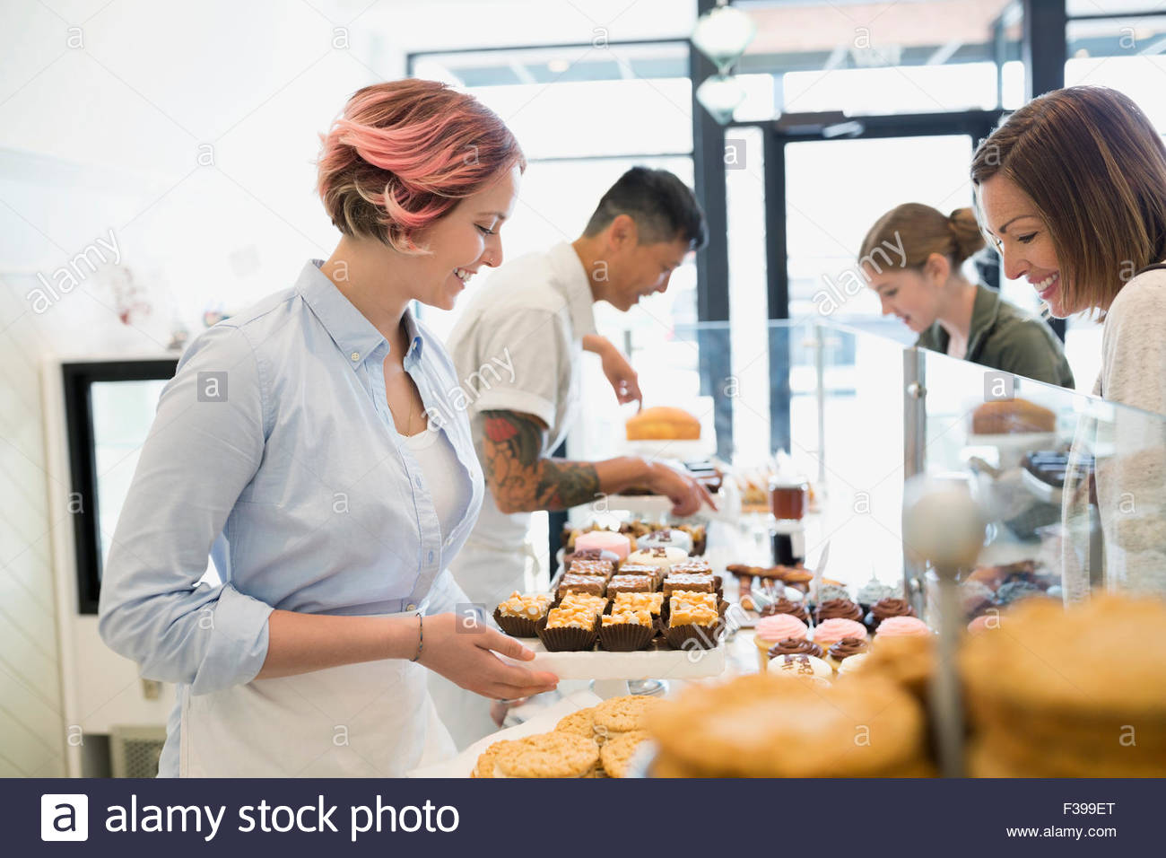 Worker serving woman pastries in bakery - Stock Image