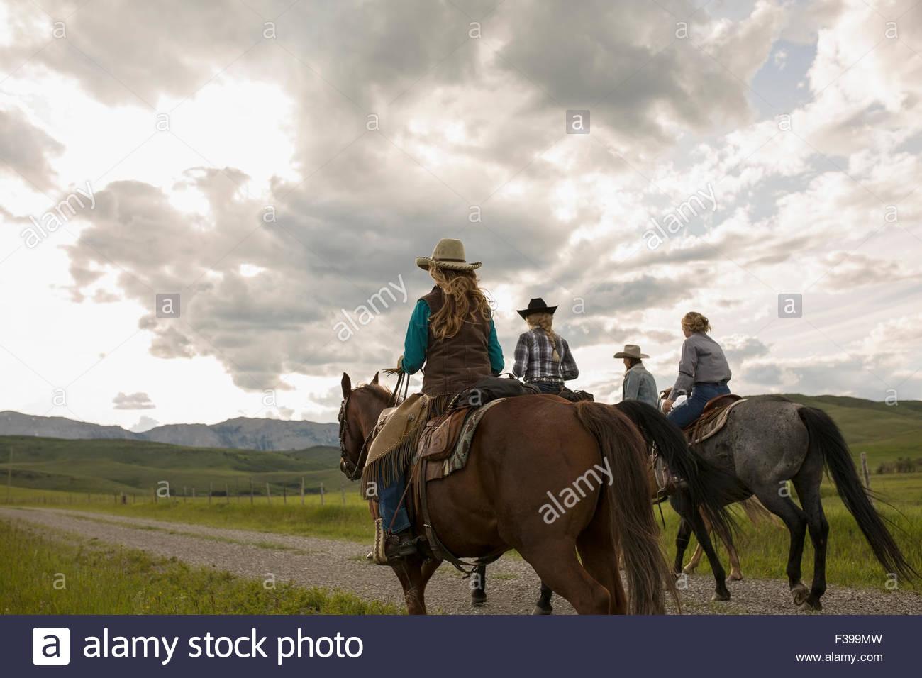 Female ranchers horseback riding on remote road - Stock Image