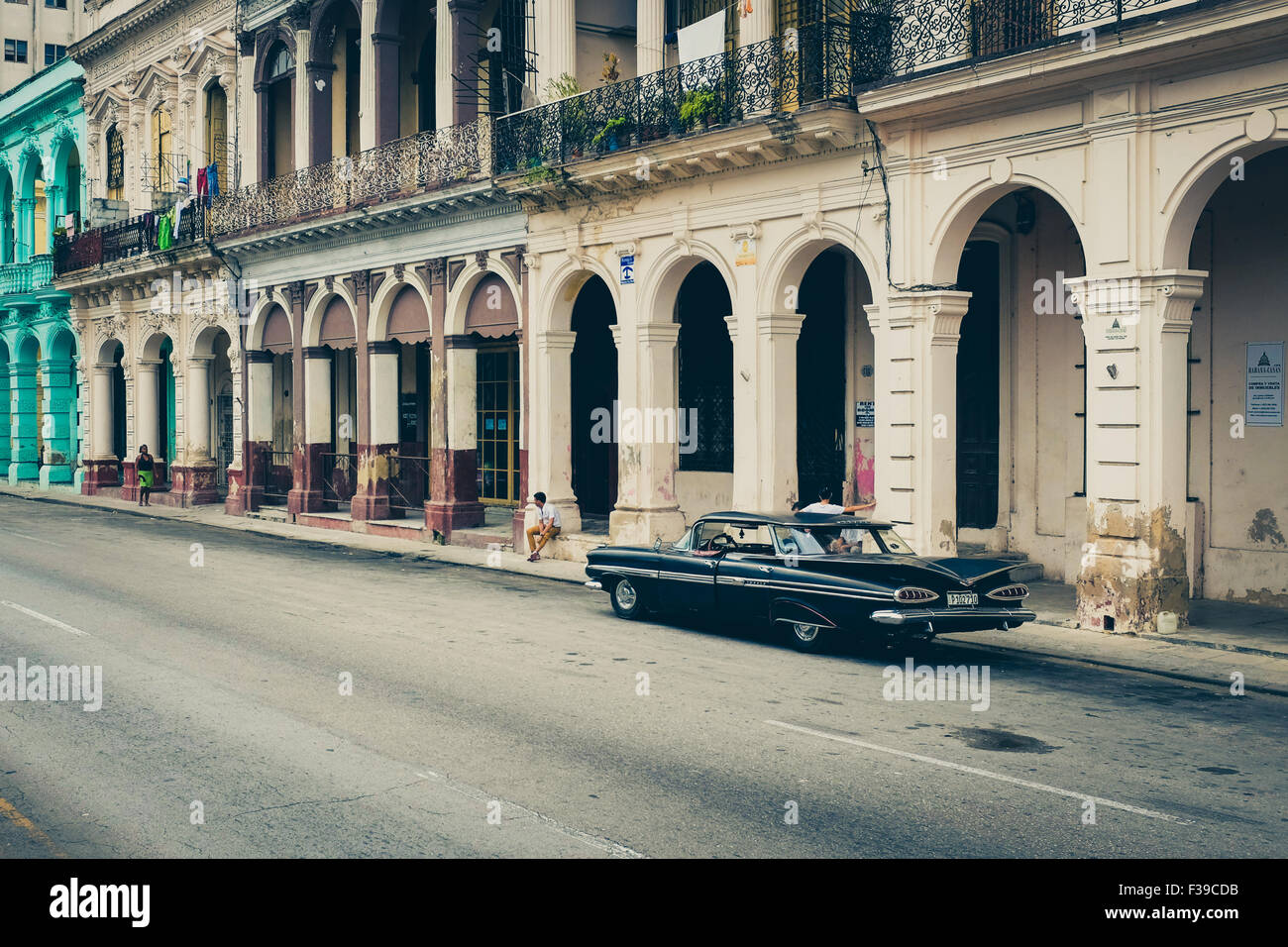A vintage black Cuban car parked on The Prado in central Havana next to colonial buildings. Cuba. - Stock Image