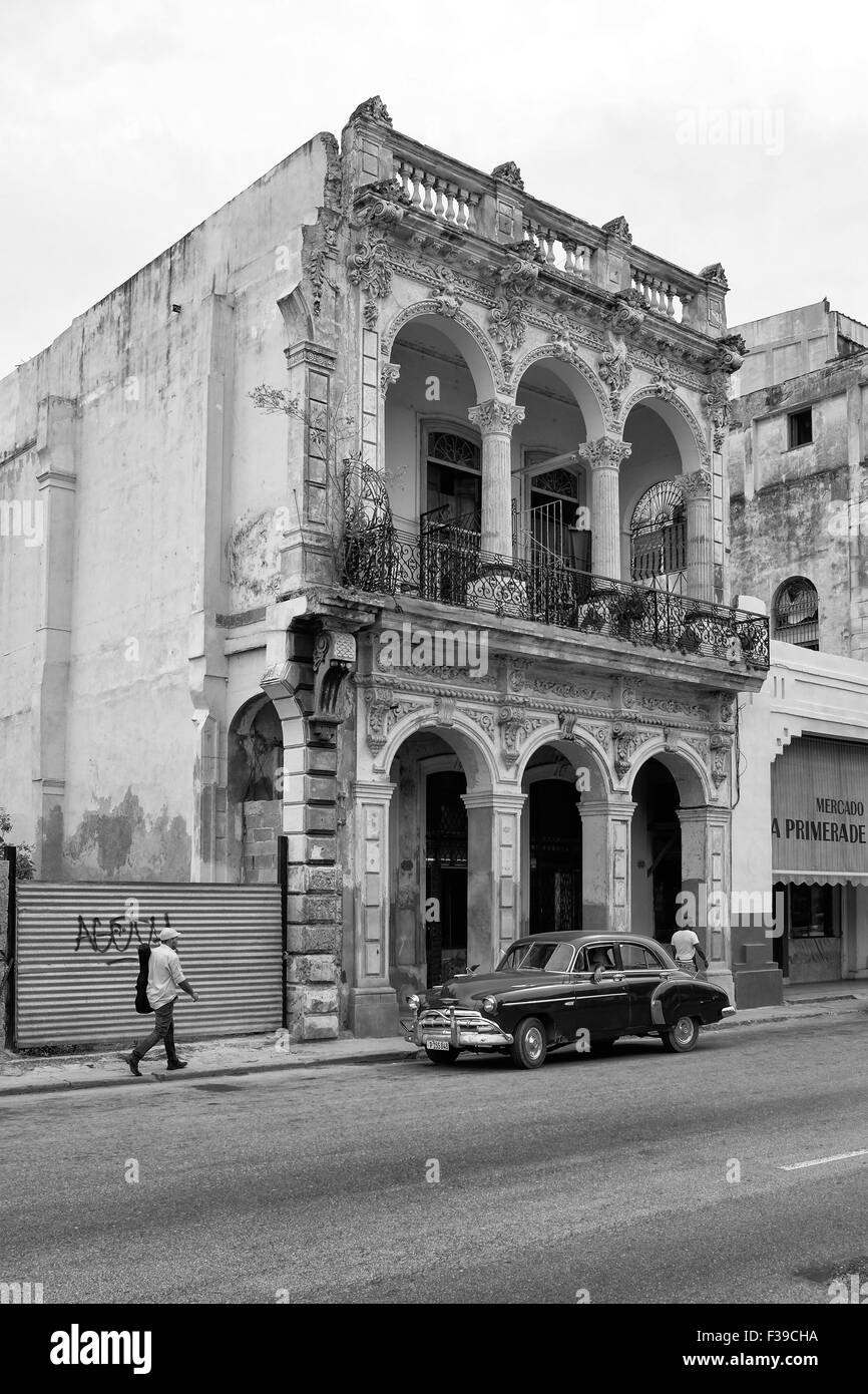 A Cuban classic car parked close to an old colonial building on the Prado a man with a guitar case walks by, Havana, - Stock Image