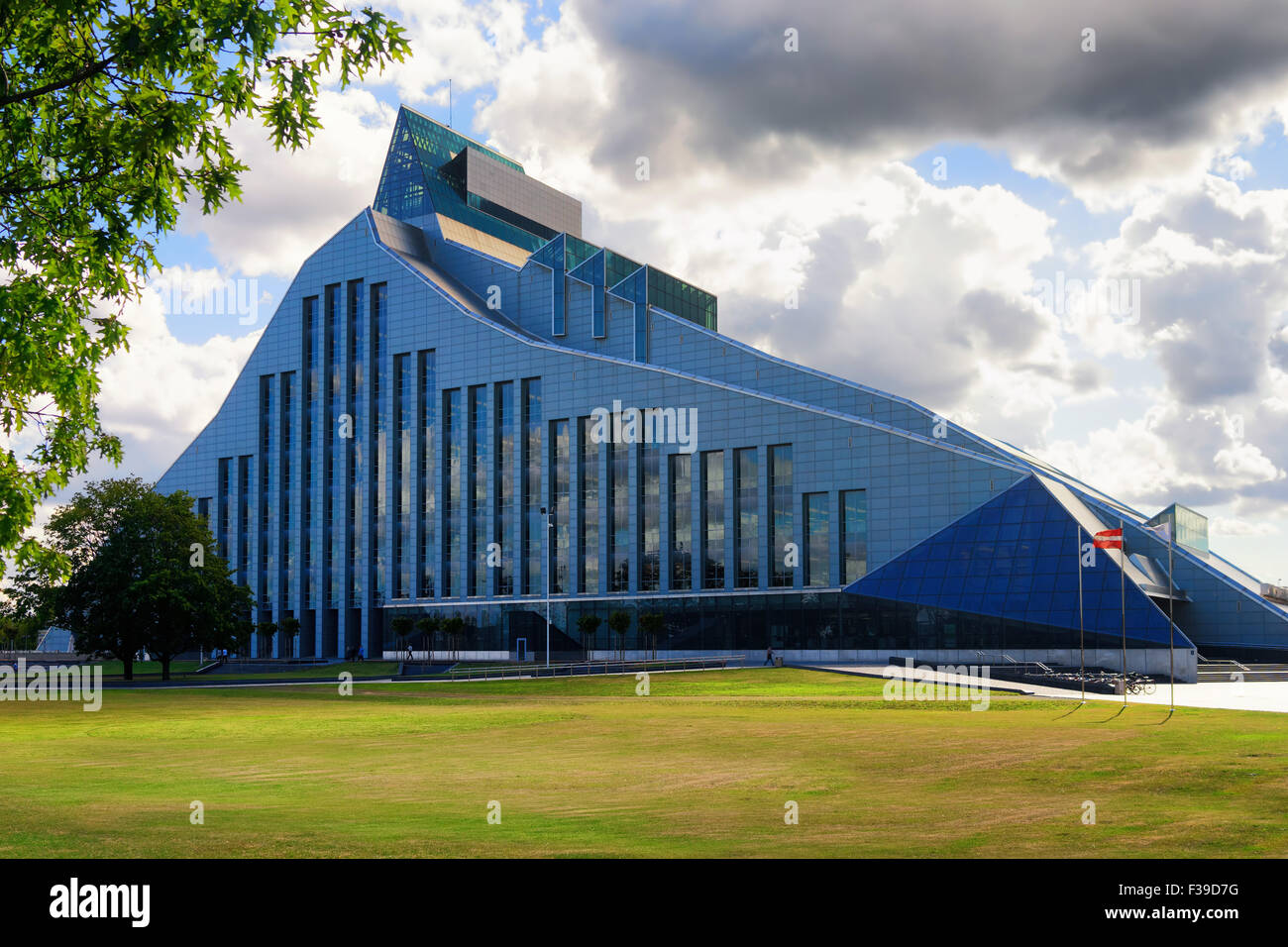 A new modern building of the Latvian National Library with the national flag on a sunny summer day with green lawn Stock Photo