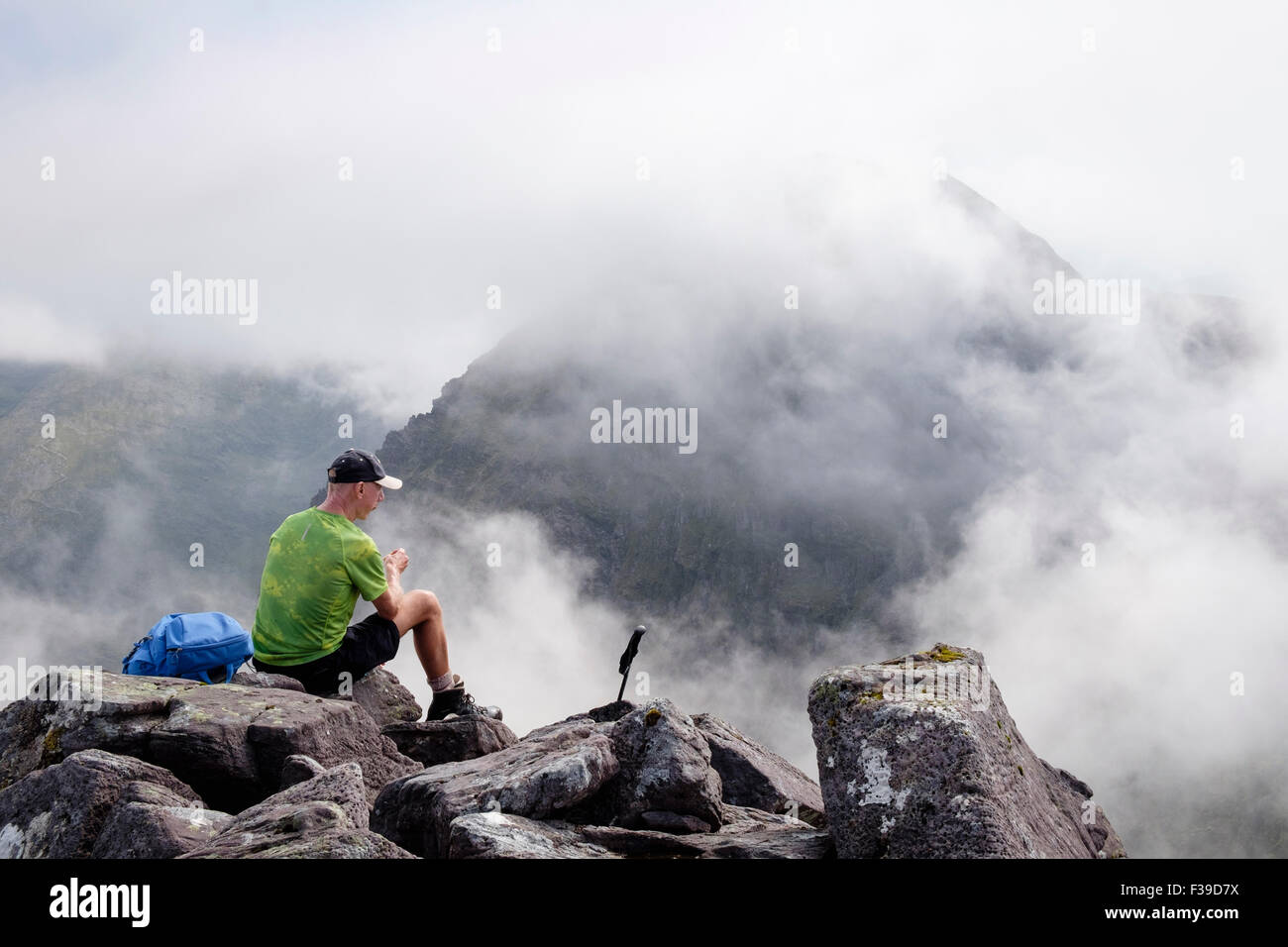 Solitary hiker resting on Beenkeragh with view to Carrauntoohil in low cloud in mountains of MacGillycuddy Reeks - Stock Image