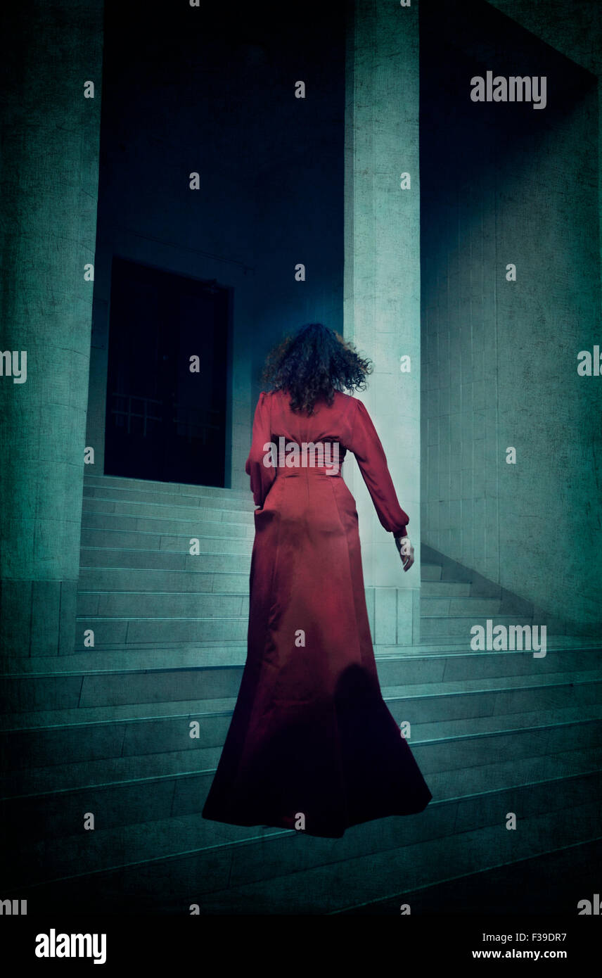 Woman in red evening dress running up stairs - Stock Image