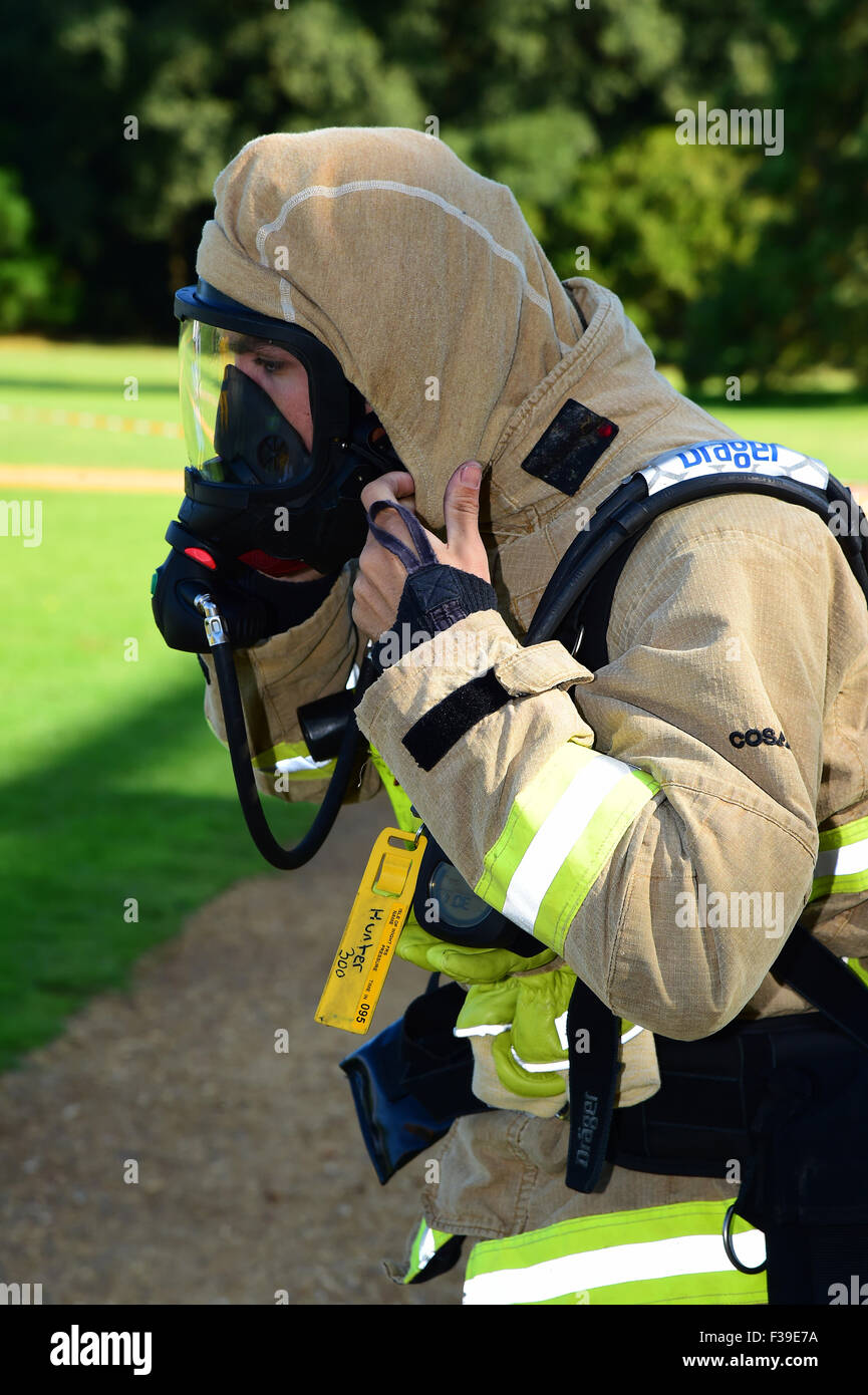 Firefighter prepares his breathing apparatus, checking his face seal, at the scene of a fire. - Stock Image