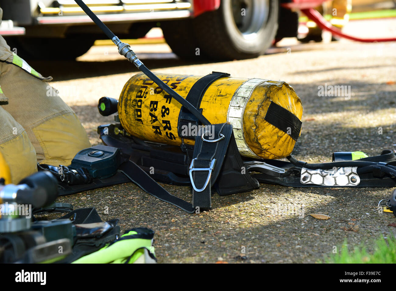 Firefighter prepares his breathing apparatus, at the scene of a fire. - Stock Image