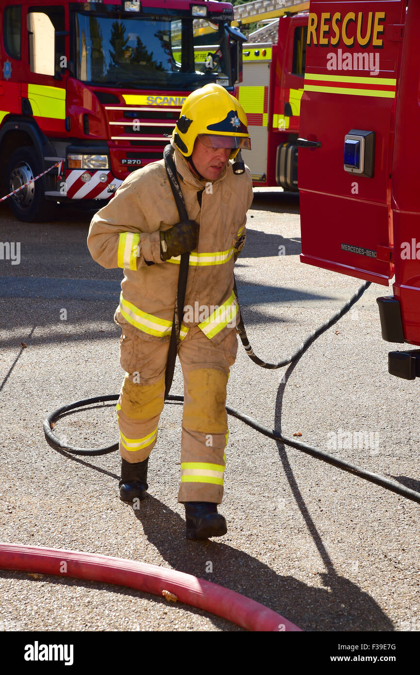 A firefighter runs out a narrow gauge hose at the scene of a fire. - Stock Image