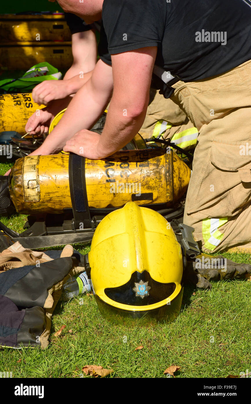 Firefighters prepare breathing apparatus at the scene of a fire. - Stock Image