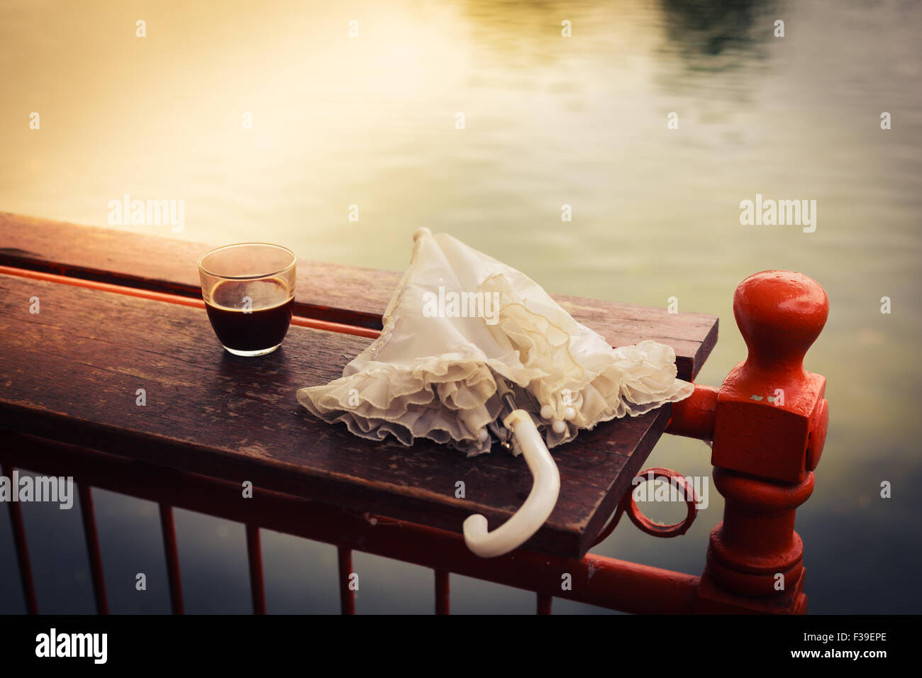 A glass of coffee and an umbrella on a wooden table by a lake in the afternoon - Stock Image