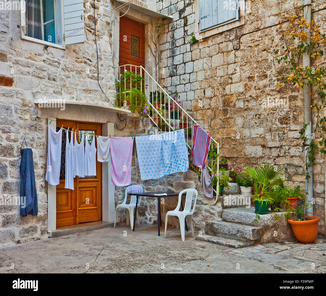 staircase full of plants and flowers leads to a Dalmatian house made of white stone blocks with laundry hanging - Stock Image