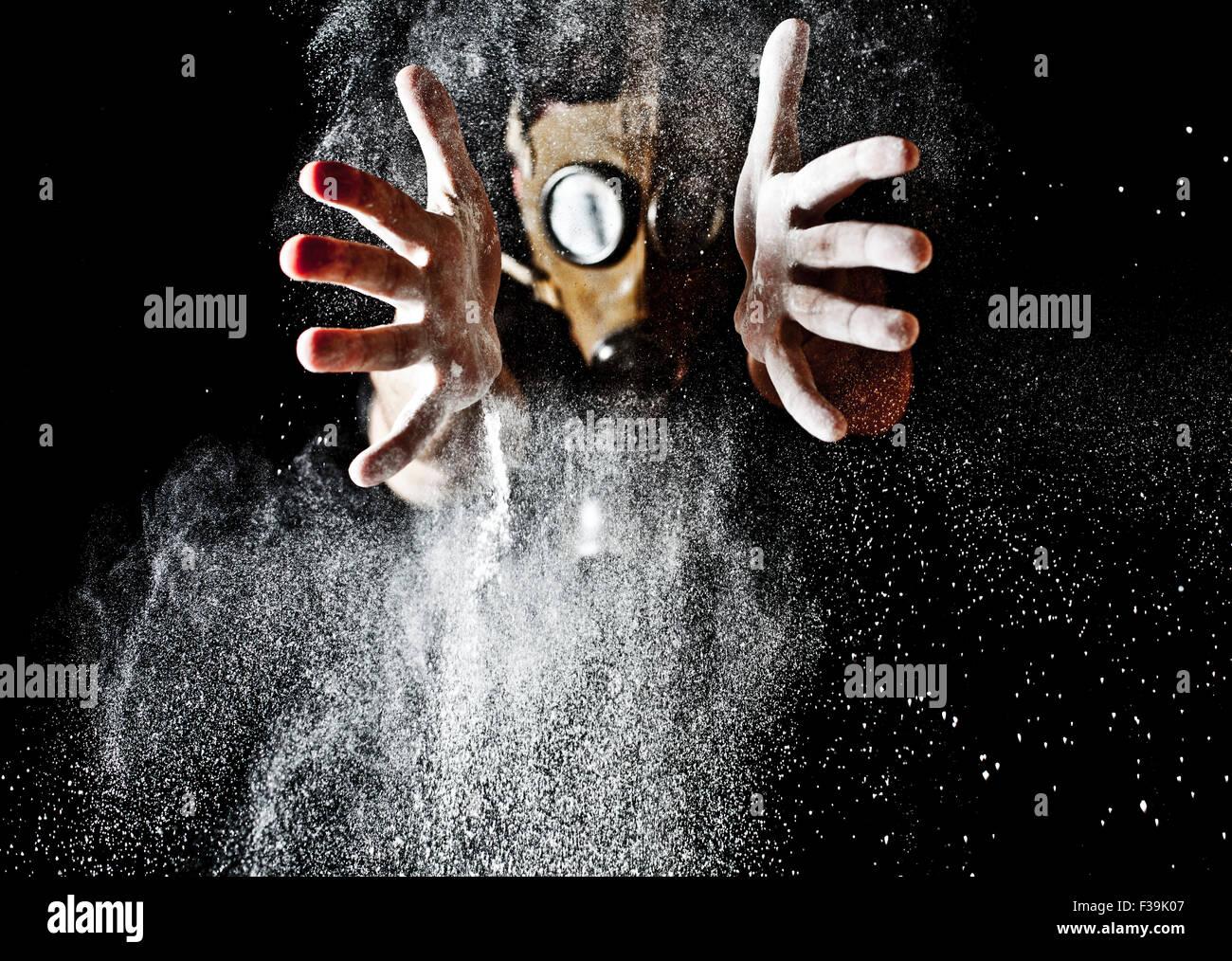 Man with gas mask throwing powder - Stock Image
