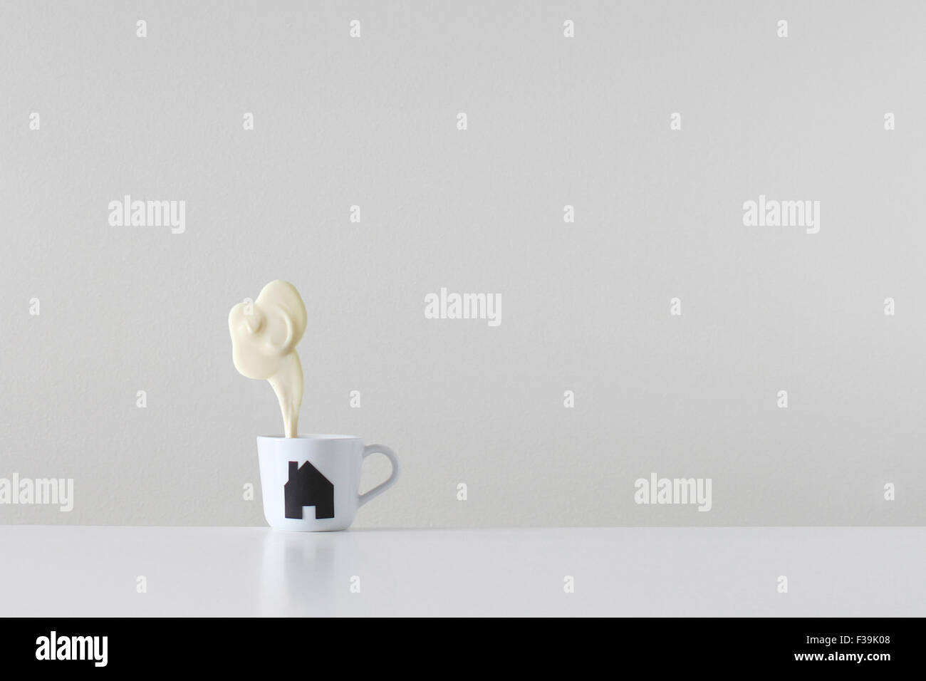 Home brew, tea cup with house silhouette print and steam made of white chocolate coming from the chimney - Stock Image