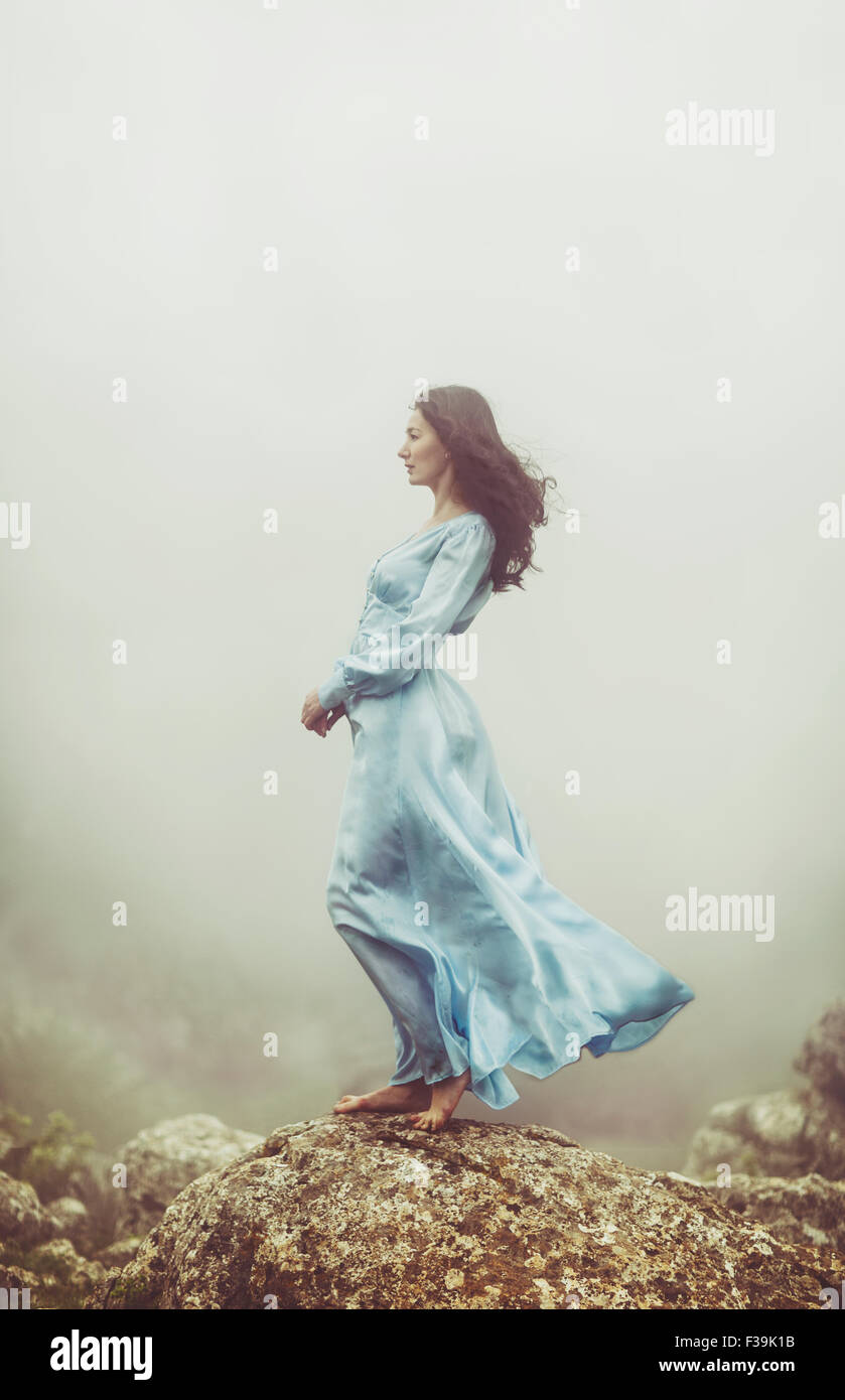 Portrait of a mid adult woman standing on rocks in the mist - Stock Image