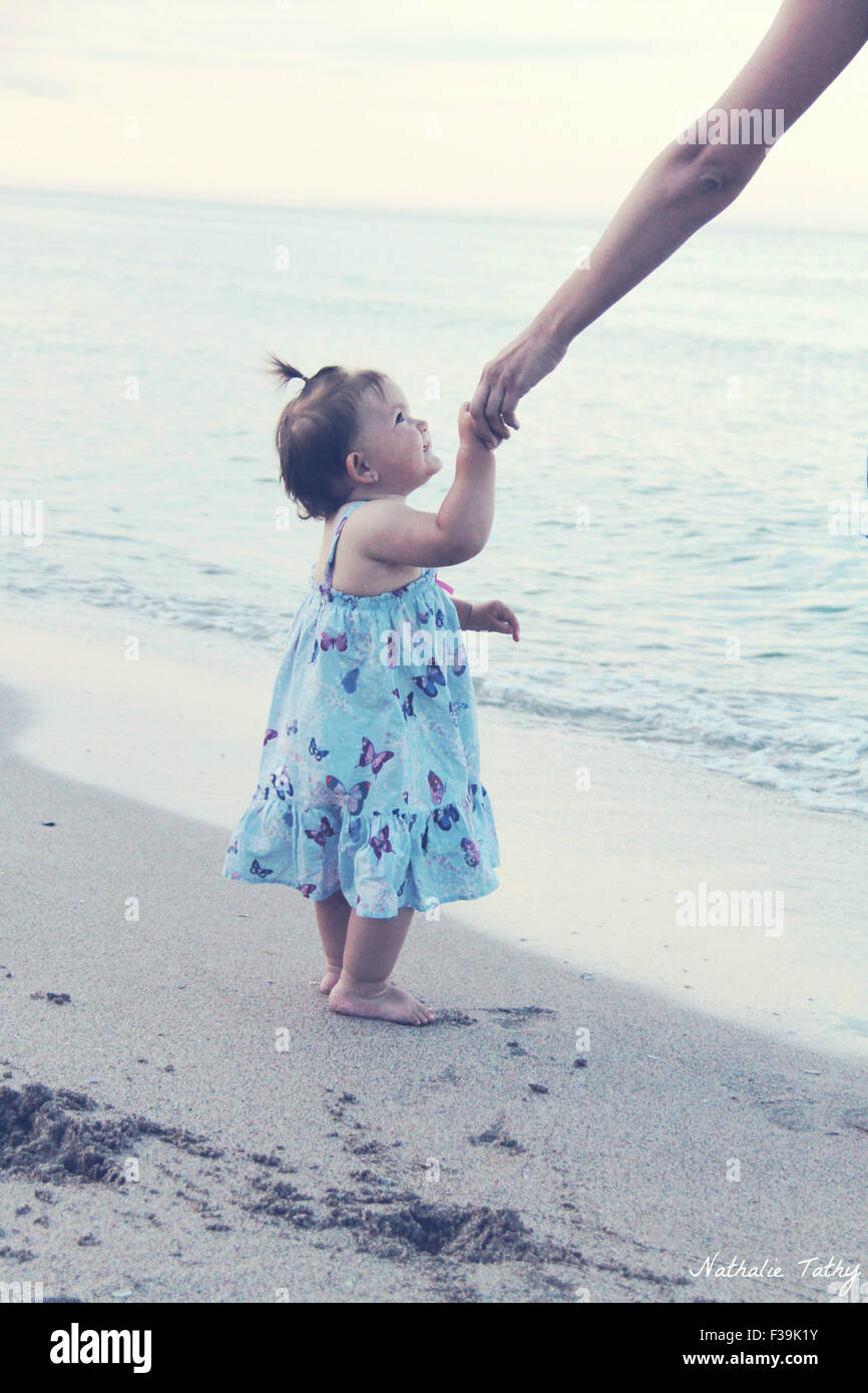 Baby girl holding her mother's hand at the beach - Stock Image