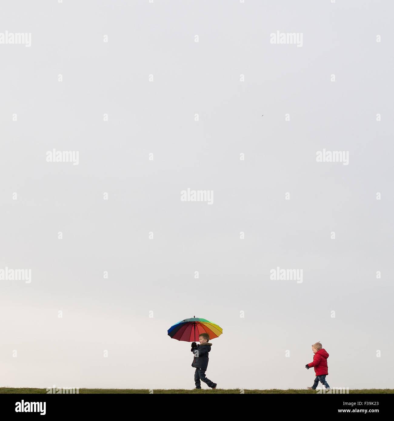 Boys walking, holding an umbrella - Stock Image
