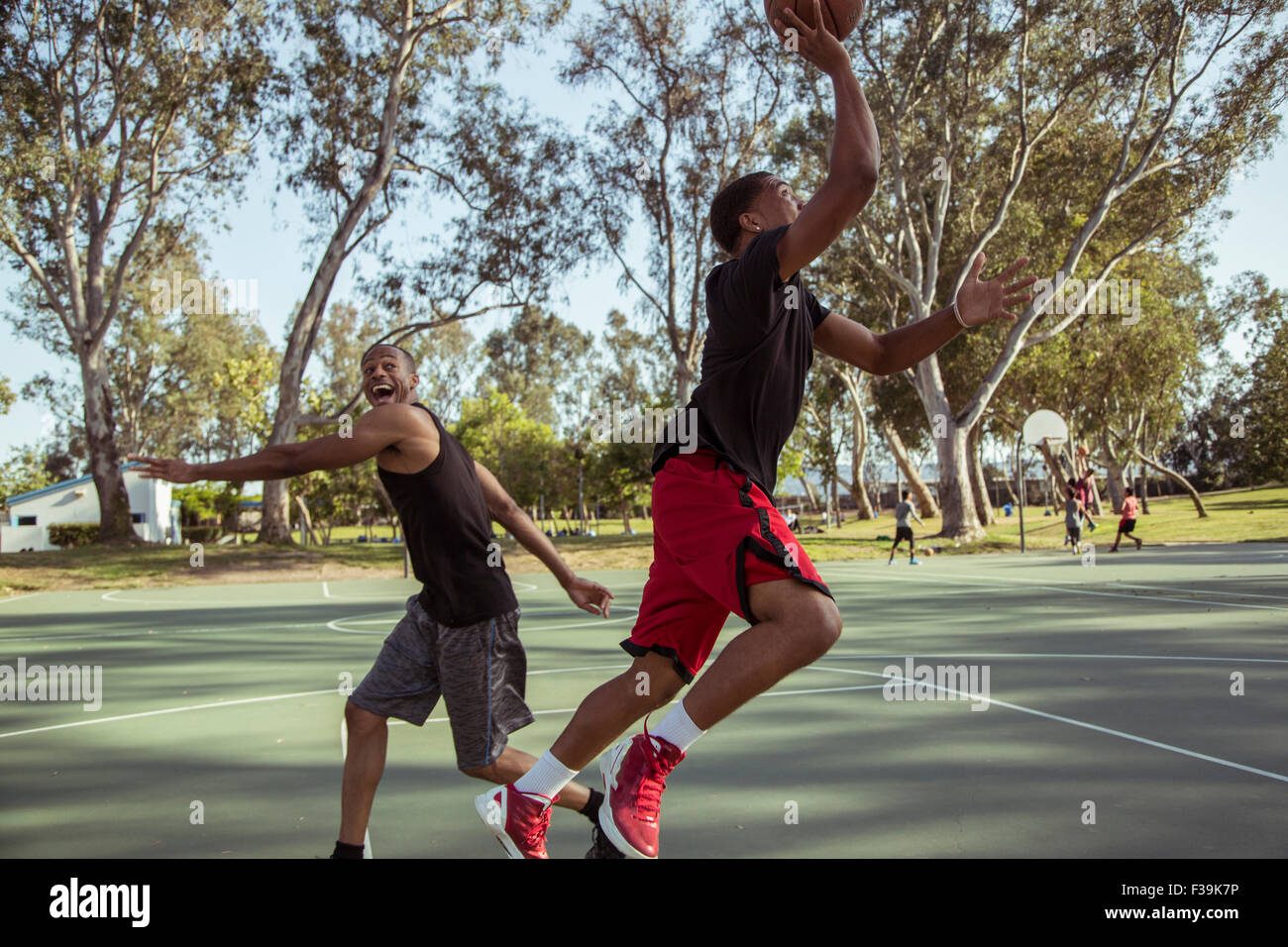 Two young men playing basketball, shooting hoops in the park at sunset Stock Photo